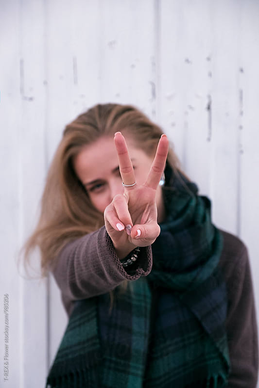 Cheerful blonde girl showing peace sign at camera by Danil Nevsky for Stocksy United