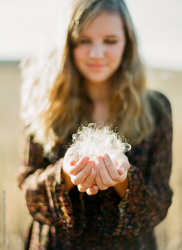 Girl playing a soy field with seed fluff by Marta Locklear for Stocksy United