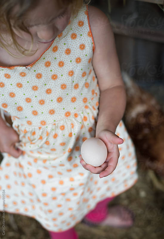 Farm girl holds a fresh egg in her hand by Cara Dolan for Stocksy United