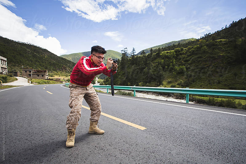 young man take picture on the road in Tibet by zheng long for Stocksy United