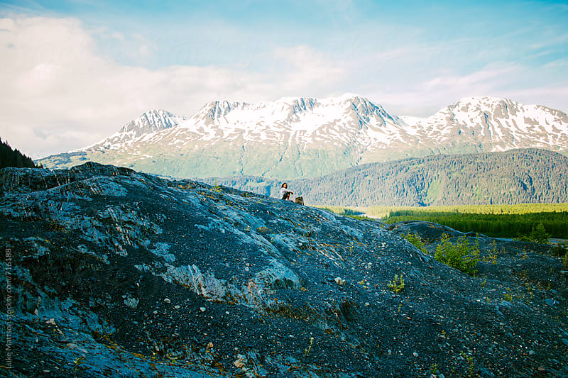 Man Sits On Top Of Hill Surrounded By Mountains In The Alaskan Wilderness by Luke Mattson for Stocksy United
