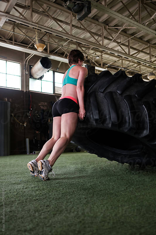 A strong woman lifts a large tractor tire in a gym by Riley Joseph for Stocksy United