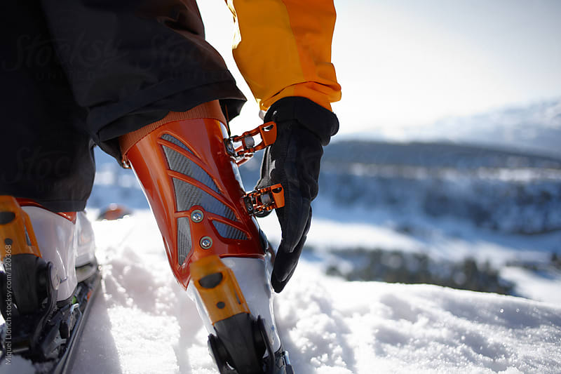 Close up of skier tighting the boots ready for skiing by Miquel Llonch for Stocksy United
