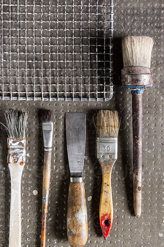 Variety of painting utensils seen from above by Melanie Kintz for Stocksy United