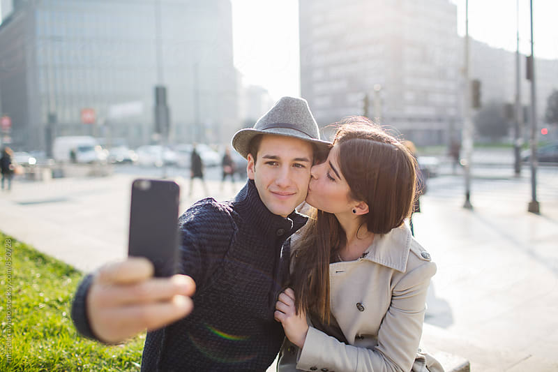 Young couple taking a selfie with kiss by michela ravasio for Stocksy United