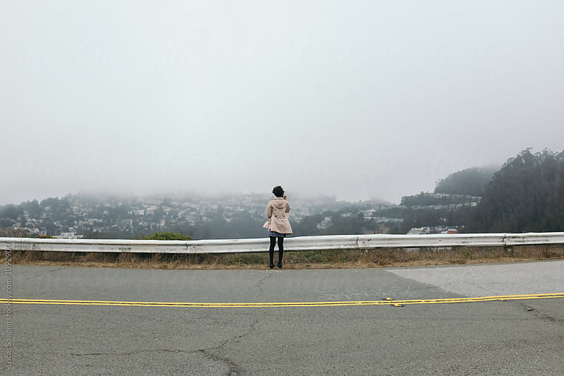 Unrecognizable tourist on road watching San Francisco in fog by Lucas Saugen for Stocksy United