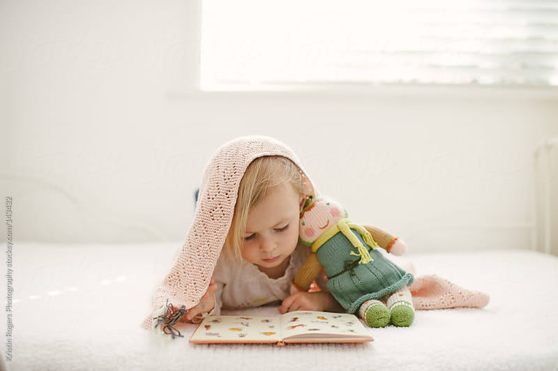 Cute toddler girl looking at book on bed with doll and blanket by Kristin Rogers Photography for Stocksy United