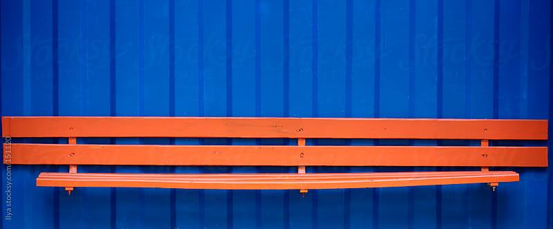 Orange bench on blue background by Ilya for Stocksy United