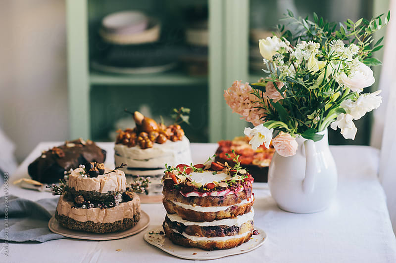 Cakes and flowers on a table by Adrian Cotiga for Stocksy United