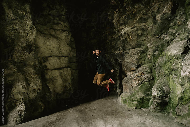 A man jumping in a cavern by Joseph West Photography for Stocksy United