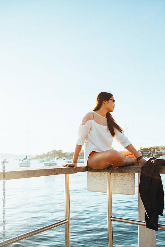 Girl sitting on pier railing by Maximilian Guy McNair MacEwan for Stocksy United