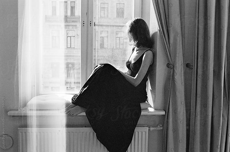Woman sitting on a windowsill by Lyuba Burakova for Stocksy United