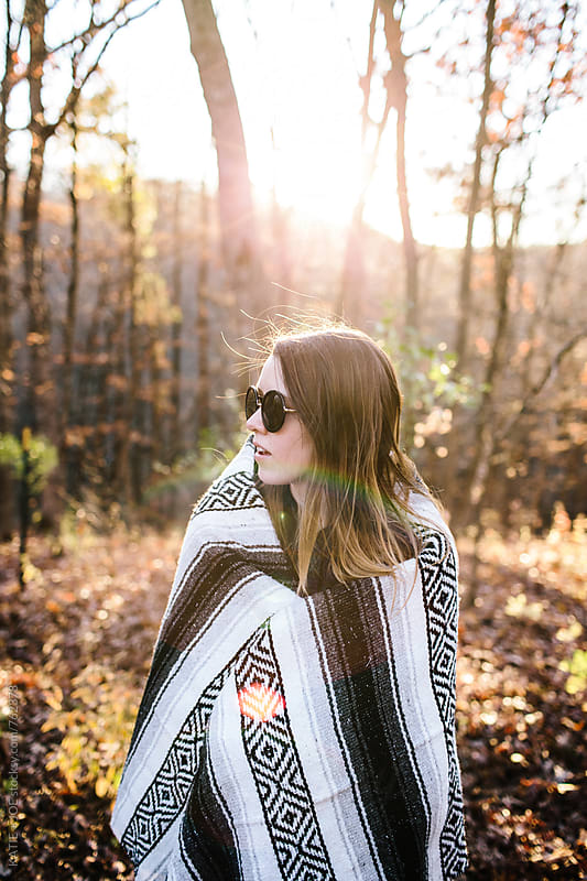 Girl bundled up with a blanket in a woods at sunset in the fall by KATIE + JOE for Stocksy United