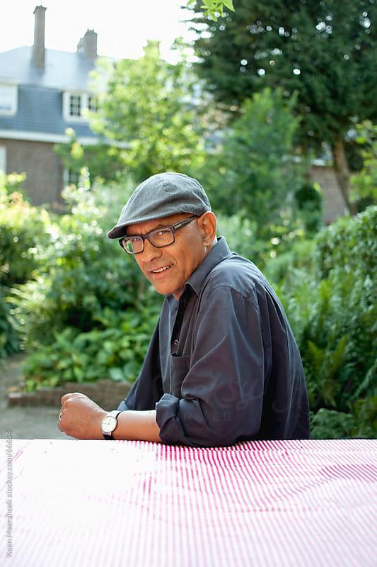 Man with retro cap sitting at a table by Koen Meershoek for Stocksy United