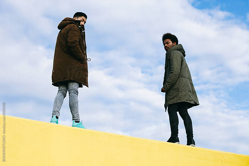 Back view of friends standing on a yellow wall. by BONNINSTUDIO for Stocksy United