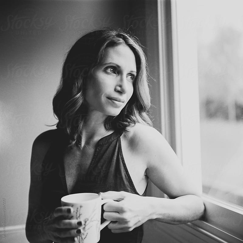 Beautiful woman by a window drinking a cup of coffee by Jakob for Stocksy United
