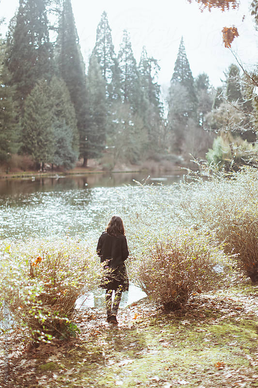 A Young Woman Walks Towards Lake by Kevin Gilgan for Stocksy United