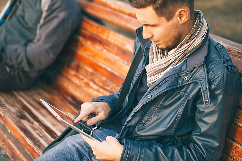 Relaxed businessman using his PC tablet while sitting on a bench by Danil Nevsky for Stocksy United