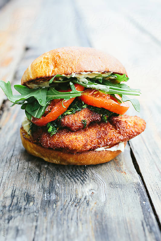 Fried chicken sandwich on bread sitting on wooden surface - digital file by Andrew Cebulka for Stocksy United