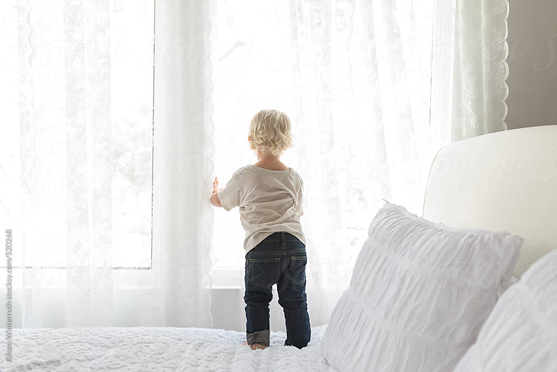 Little Boy Looks Through Window While Standing On Bed by Alison Winterroth for Stocksy United