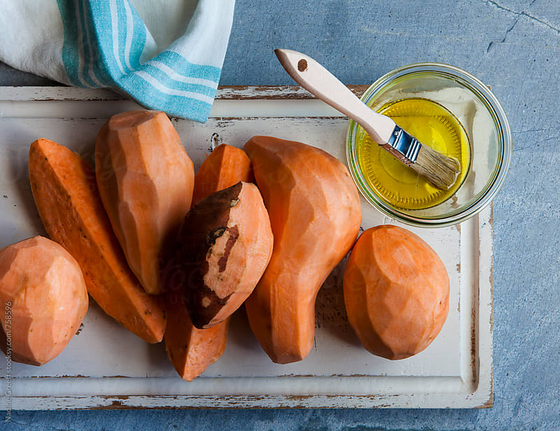 Raw, peeled sweet potatoes with olive oil as seen from above by Nadine Greeff for Stocksy United