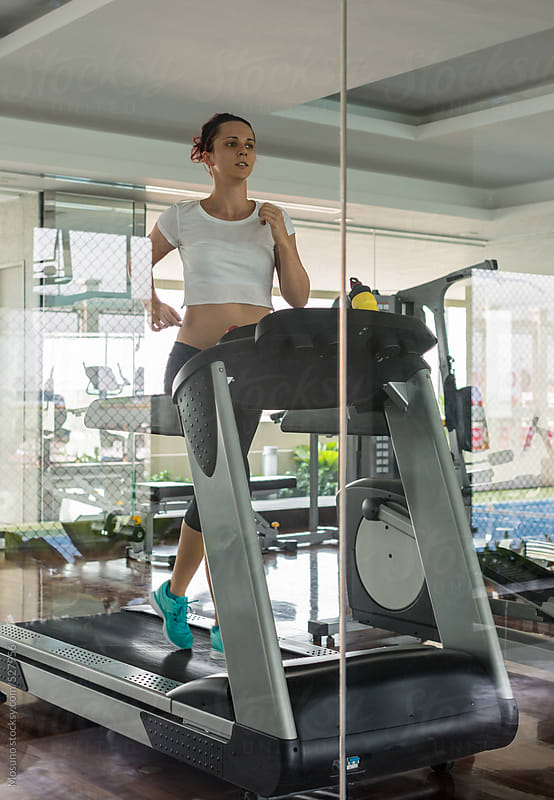 Woman Running on a Treadmill by Mosuno for Stocksy United