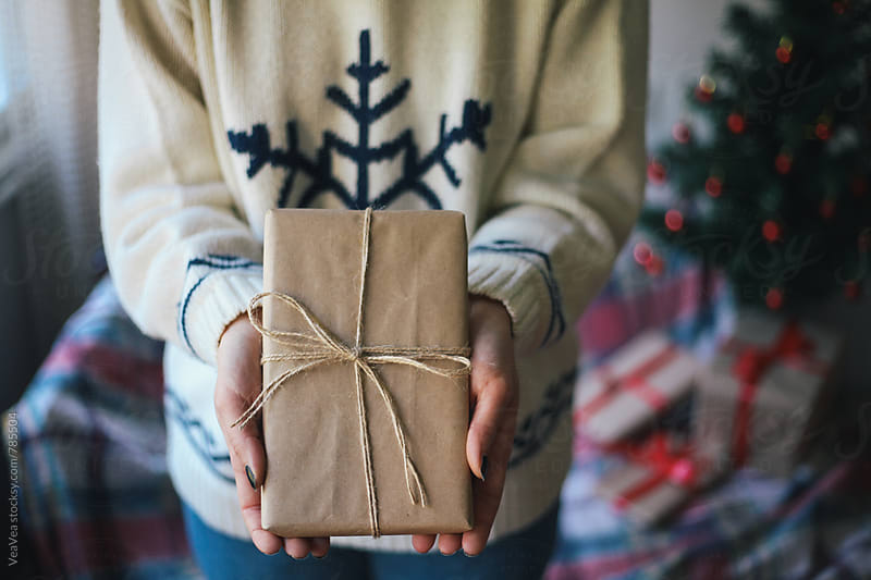 Woman in a Christmas sweater holding a Christmas present  by Marija Mandic for Stocksy United