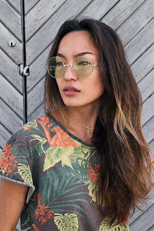 Serious asian girl in sunglasses looking away by Danil Nevsky for Stocksy United