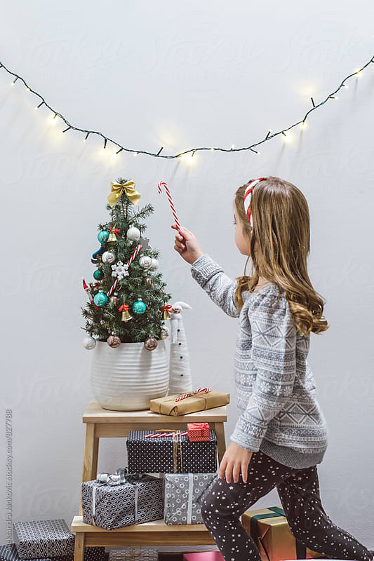 Little Girl Decorating Christmas Tree with Sugar Cane Ornament by Aleksandra Jankovic for Stocksy United