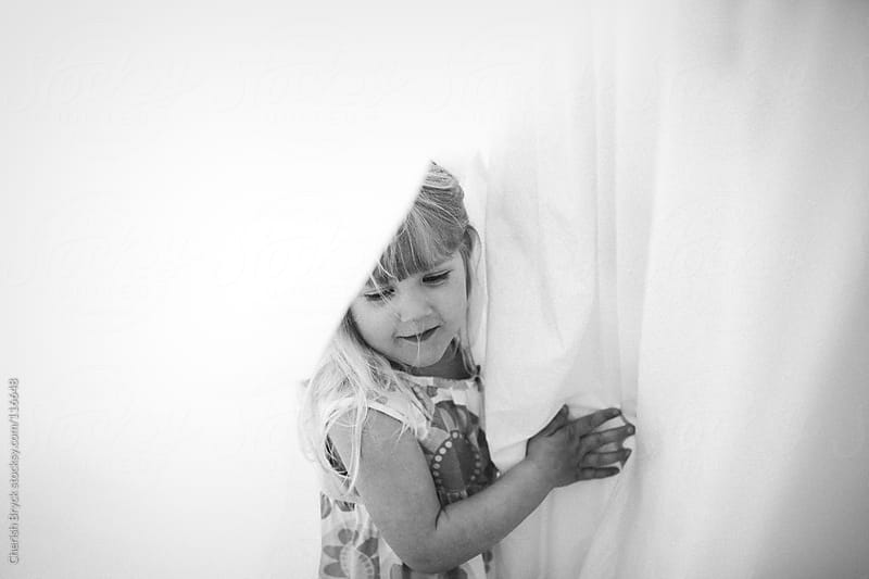 A little girl in between the sheets on a clothing line. by Cherish Bryck for Stocksy United
