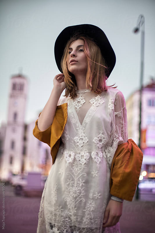 Beautiful fashionable woman walking on the streets at night by Maja Topcagic for Stocksy United