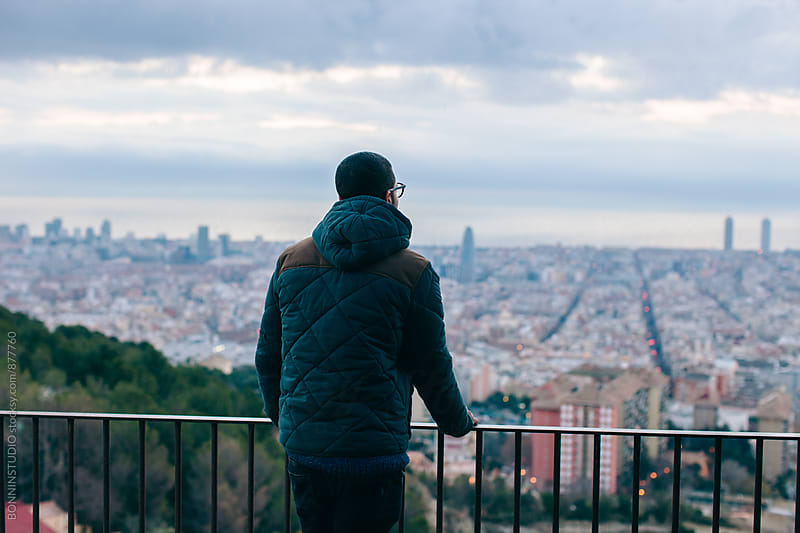 Back view of a man standing above city on winter. by BONNINSTUDIO for Stocksy United