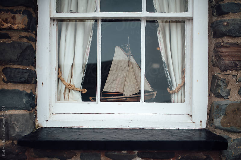 Wooden sailboat sitting on a windowsill by Suzi Marshall for Stocksy United