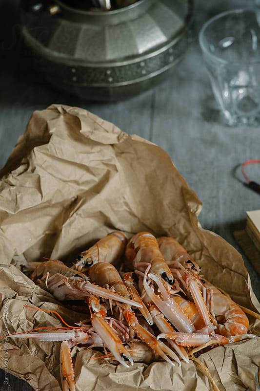 Langoustines on kitchen table. by Darren Muir for Stocksy United
