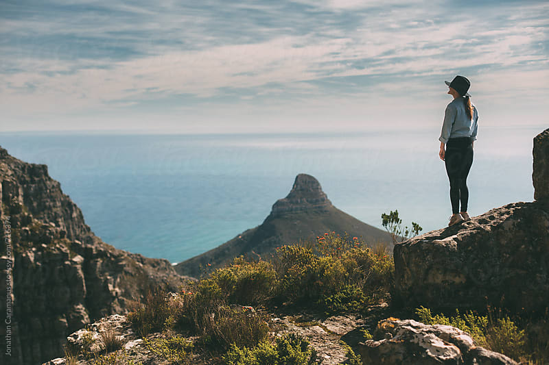 Young woman standing on mountain overlooking view and ocean by Jonathan Caramanus for Stocksy United