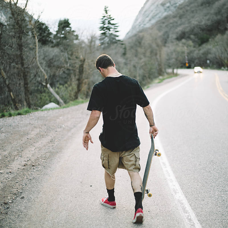 Skateboarder Holding Board by Jake Elko for Stocksy United