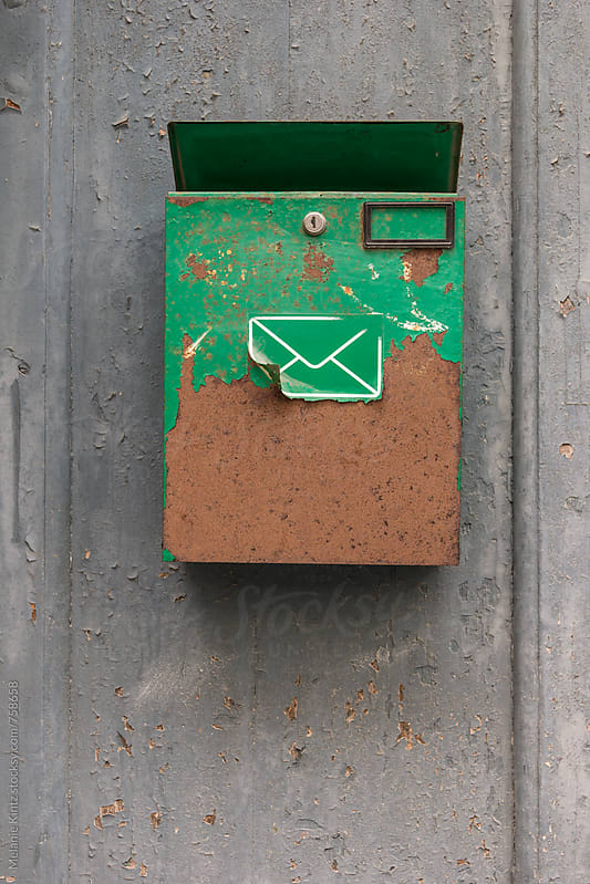 Green and rusty letterbox on a door by Melanie Kintz for Stocksy United