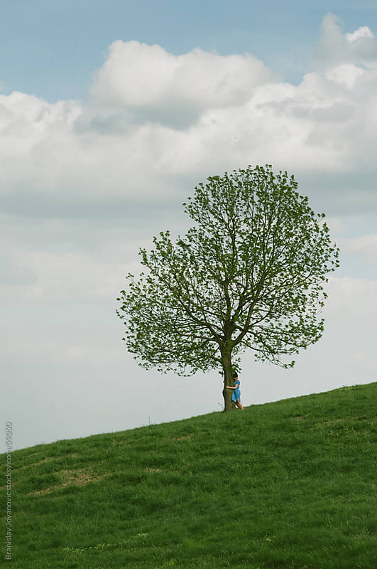 Girl hugging a single tree on a hill by Branislav Jovanović for Stocksy United