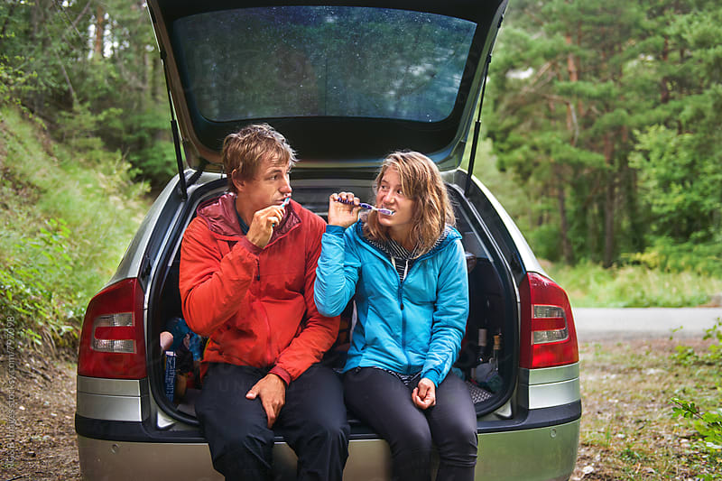 Couple sitting in the car's open trunk, brushing their teeth by RG&B Images for Stocksy United