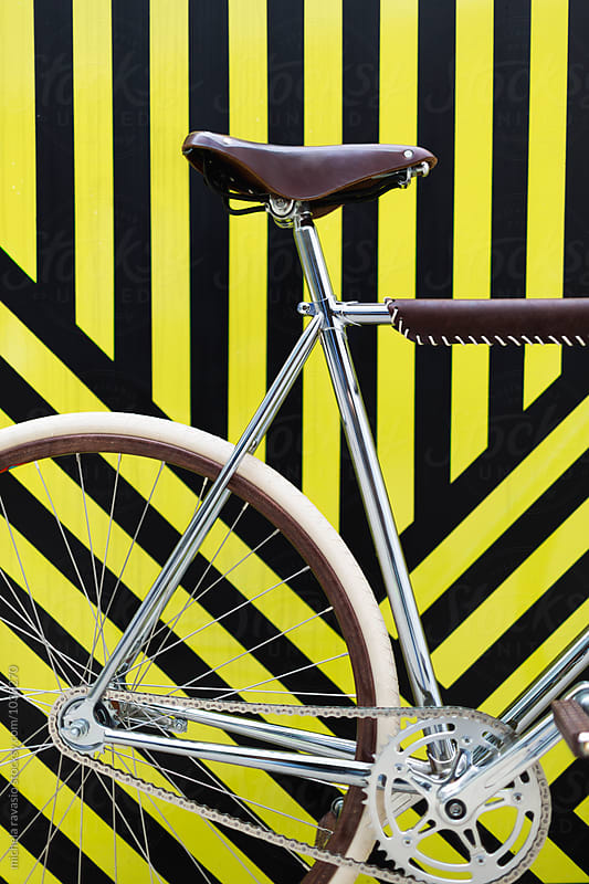 Bicycle on black and yellow stripes by michela ravasio for Stocksy United