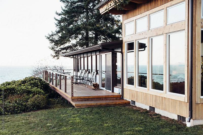 Back Porch And Lawn Of Island Vacation Home Surrounded By Ocean by Luke Mattson for Stocksy United