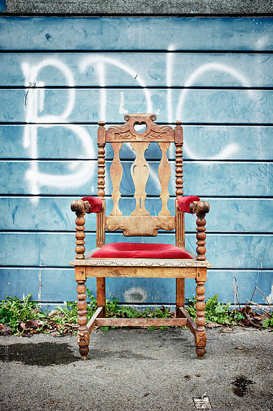 An ornate chair by a garage door by James Ross for Stocksy United