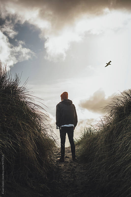 Young Man Standing on Coastal Hill by Evan Dalen for Stocksy United