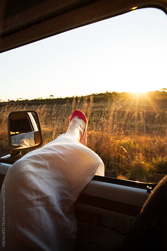 Road Tripping - Woman Stretching Her Leg Outside Window While Driving at Sunset Time by Julien L. Balmer for Stocksy United