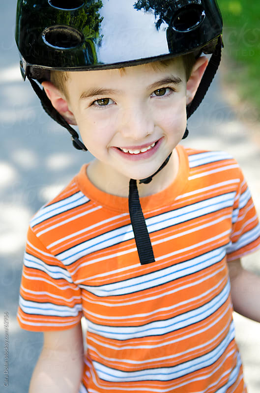 Happy boy wears bicycle helmet by Cara Dolan for Stocksy United