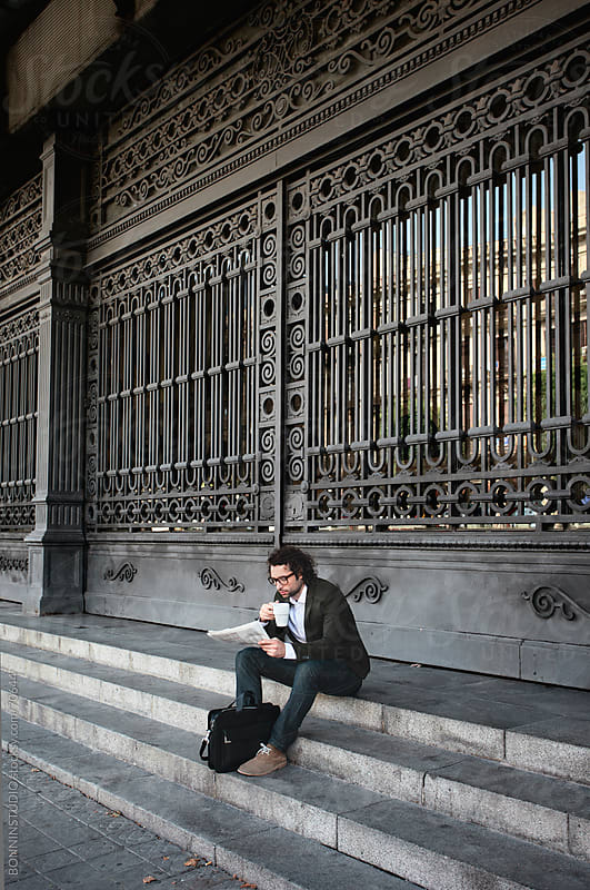 Young modern businessman reading newspaper waiting in front a big iron door on a train station.  by BONNINSTUDIO for Stocksy United