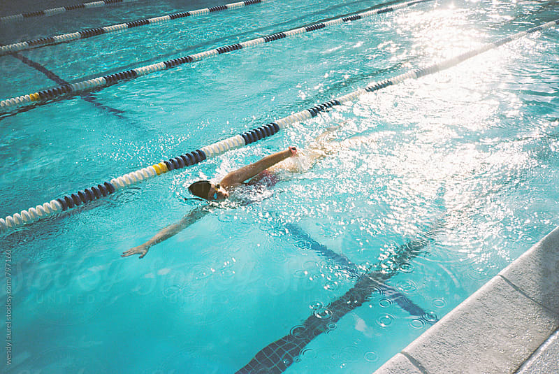 swimmer swimming freestyle in pool with lane lines and sunshine on film by wendy laurel for Stocksy United