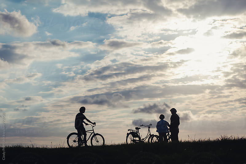 Silhouettes of a father and his sons with their bicycles getting ready to go for a ride by Cindy Prins for Stocksy United