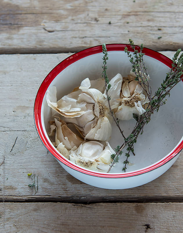Heads of garlic with thyme in a bowl by Marta Muñoz-Calero Calderon for Stocksy United