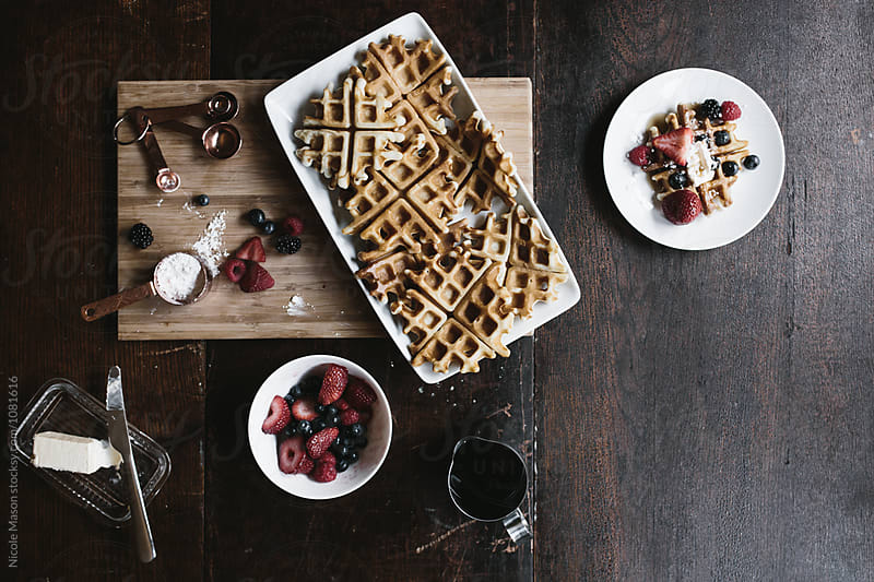 layout of waffles and ingredients on wood table by Nicole Mason for Stocksy United